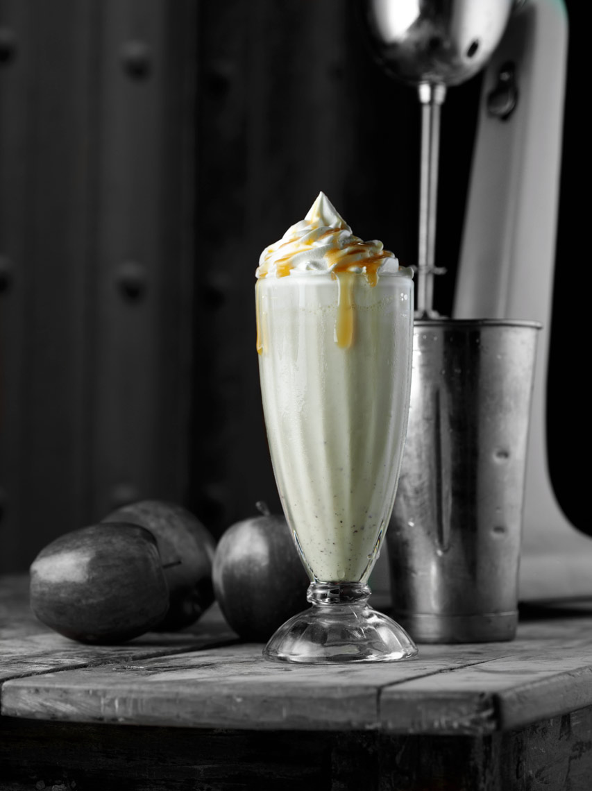 Carmel apple milk shake with whip cream and Carmel sauce on rustic wood table with apples and Hamilton beach blender Fantich studio food photography