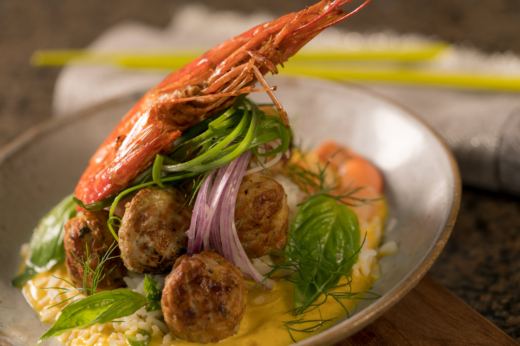 Meatballs and whole prawns with rice garnished with onions and basil in a rustic bowl  on wood en surface Fantich studio food photography.